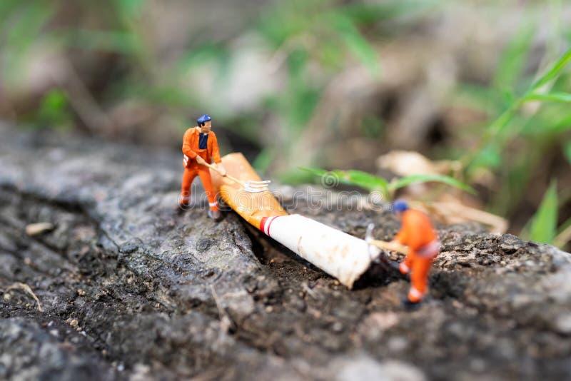 Miniaturleute: Arbeitskraft zerstören Zigaretten, die die Luftverschmutzung ist, die für Leute nicht sicher ist Verwenden Sie Bil stockfoto