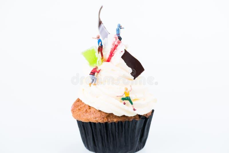 Miniaturleute auf dem Bereifen des Abschlusses des kleinen Kuchens oben lizenzfreies stockbild