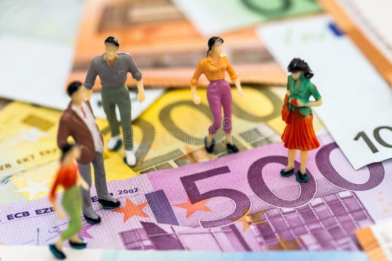Miniaturleute auf Eurobanknoten stockbild