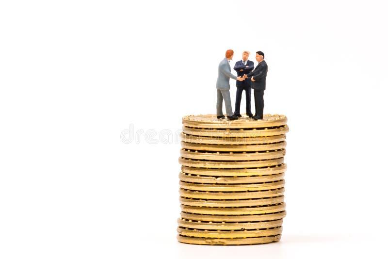 Miniaturleute auf Goldmünze und rütteln Hand, Geschäft concep stockbilder