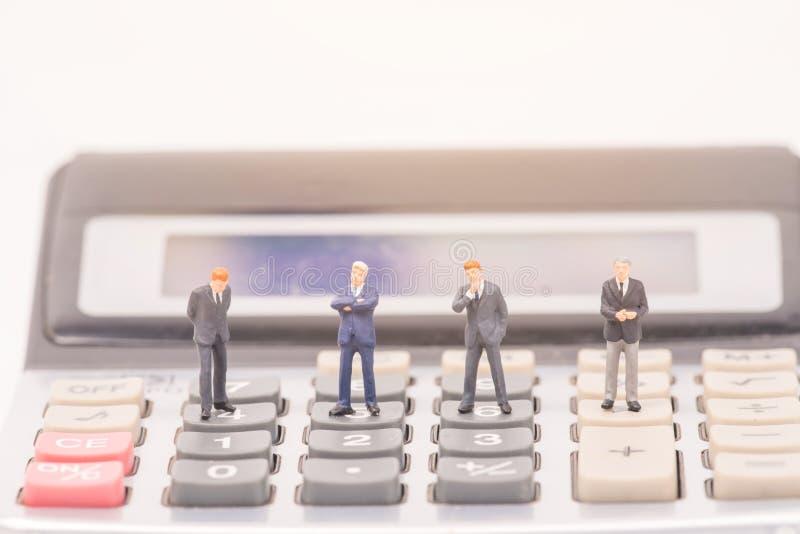 Miniaturleute auf Taschenrechner lizenzfreie stockfotografie