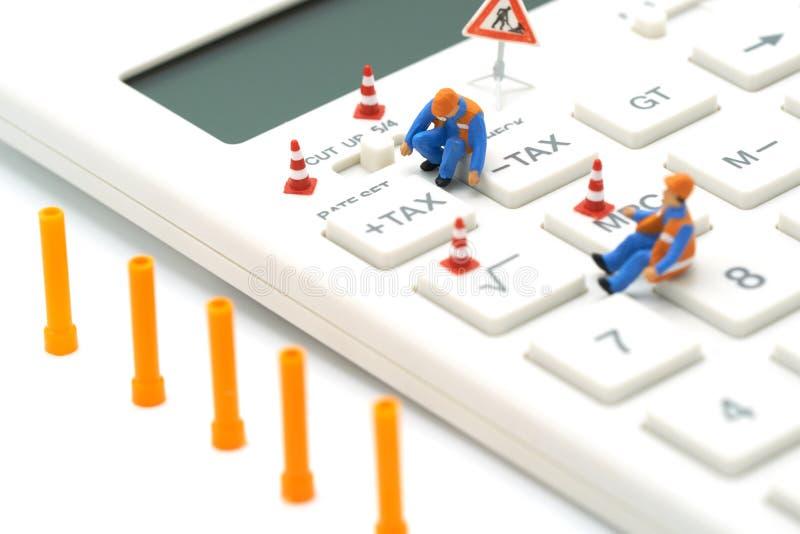 Miniaturleute Bauarbeiter-Keypad-STEUER-Knopf für Steuerberechnung Einfach zu berechnen auf weißem Taschenrechner auf weißem back lizenzfreies stockbild