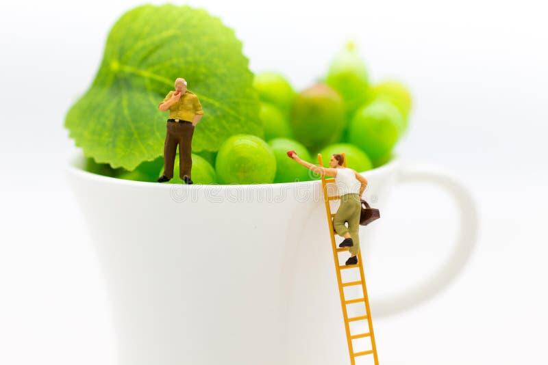 Miniaturleute: Bemannen Sie Gebrauch die Treppe und geben Sie dem alten Mann die Frucht Bildgebrauch für das Teilen zwischen Alte stockfotos