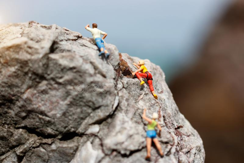 Miniaturleute: Bergsteiger, der oben beim Klettern der Herausforderung schaut stockbilder