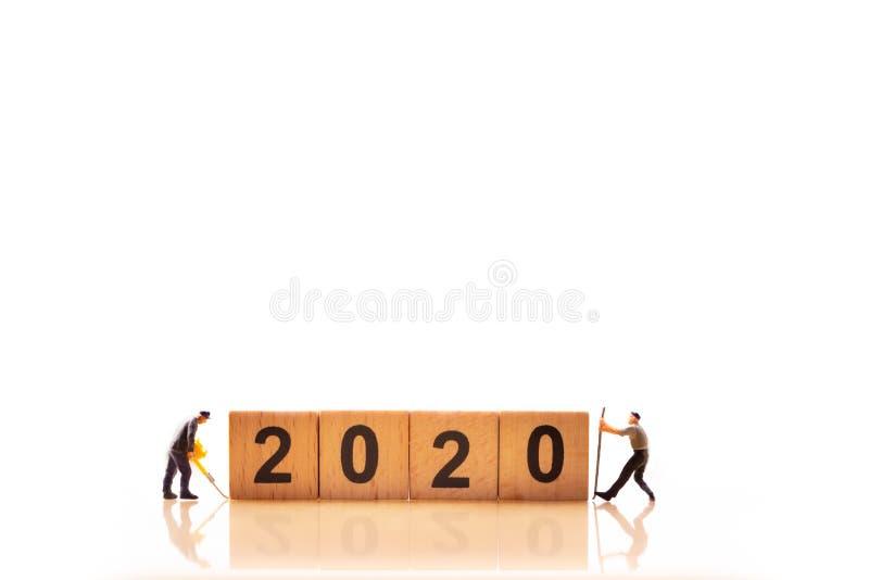 Miniaturleute Das Wort ?2020 ?der W?rfel Miniaturarbeitskr?fte auf lokalisiertem wei?em Hintergrund stockfotos