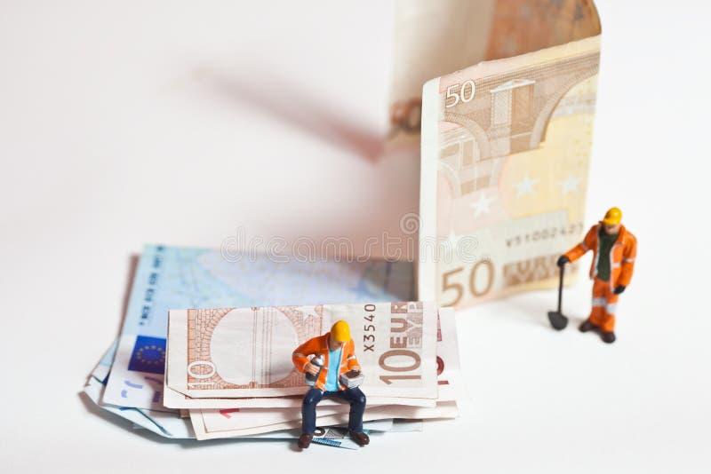 Miniaturleute in der Aktion mit Eurobanknoten stockbild