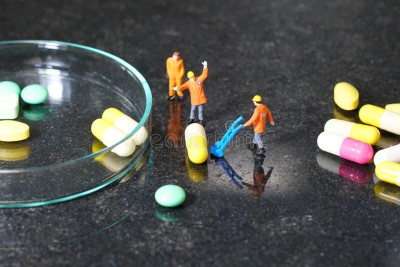 Miniaturleute - die Arbeitskraft bei der Arbeit mit Medizinpillen lizenzfreie stockfotos