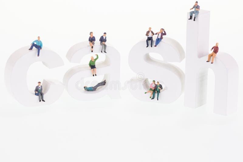 Miniaturleute, die auf hölzernen Buchstaben des Bargeldes sitzen lizenzfreie stockfotografie