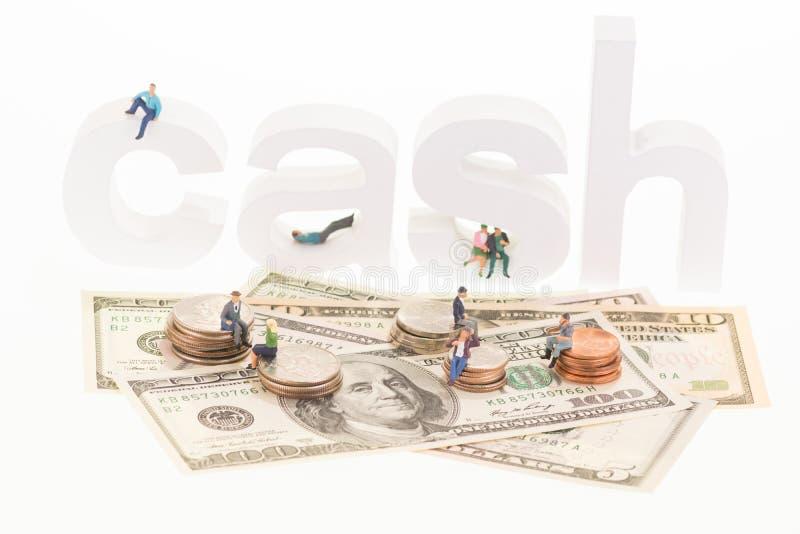 Miniaturleute, die auf hölzernen Buchstaben und Münzen des Bargeldes sitzen stockfotografie
