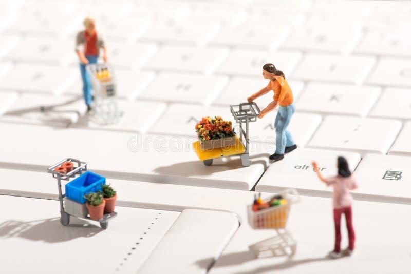 Miniaturleute, die für Einzelteile mit Warenkörben kaufen lizenzfreie stockfotografie