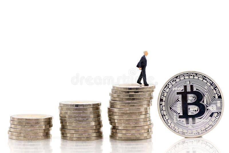 Miniaturleute: Die Geschäftsmänner, die auf einer Münze gestapelt wird stehen, erhöhen sich oben beziehungsweise, verwendet als G stockbilder