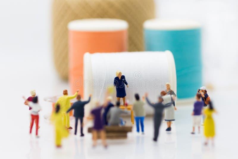 Miniaturleute: Die Gruppen-Frauen, die Fabrikprotest Bildgebrauch für Ansprüche oder Nutzen spinnen, sollten von der harten Arbei lizenzfreie stockfotos