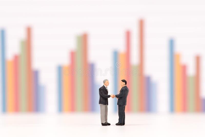 Miniaturleute, die Hand auf Geschäftsdiagrammhintergrund rütteln stockfoto