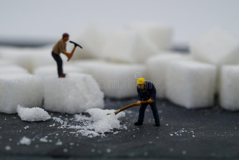Miniaturleute, die mit Zucker arbeiten Stellen Sie schützende Schablone und die Pille gegenüber, die im Hintergrund verwischt wir lizenzfreie stockfotos