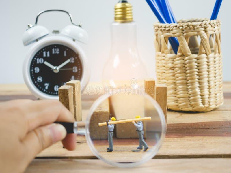 Miniaturleute führen Arbeitskraft auf hölzerner Tabelle und weißem Hintergrund aus lizenzfreies stockfoto