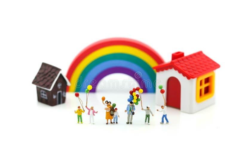Miniaturleute: Familie mit Ballon- und Regenbogenhintergrund, herein stockfoto