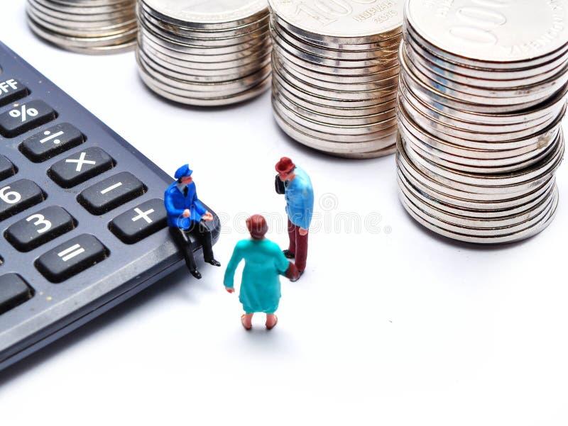 Miniaturleute: Geschäftsleute mit Taschenrechner- und Münzenstapeln stockfotos