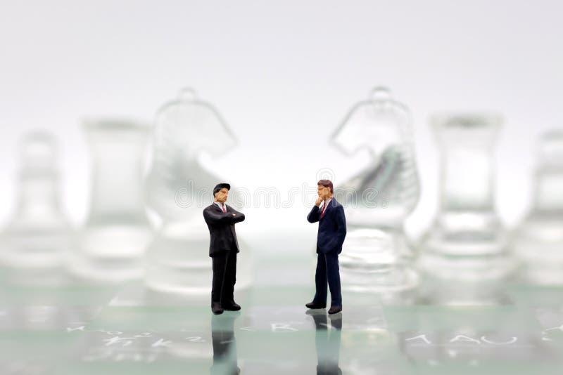 Miniaturleute, Geschäftsmänner stehen auf Gegenseiten des Schachspiels, unterschiedliche Partei, Nutzen, Gebrauch als Geschäftswe stockbild