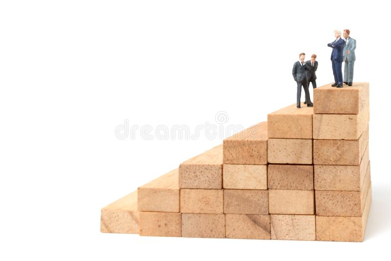 Miniaturleute: Geschäftsmann, der auf hölzernem Block steht stockfoto