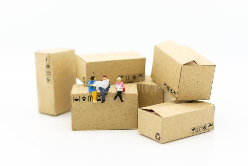 Miniaturleute: Geschäftsmann, der auf Kasten im Lager sitzt Bildgebrauch für Geschäfts-, industrielles und logistischeskonzept stockfotografie