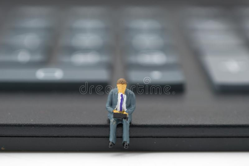 Miniaturleute: Geschäftsmann, der auf Taschenrechner sitzt stockbild