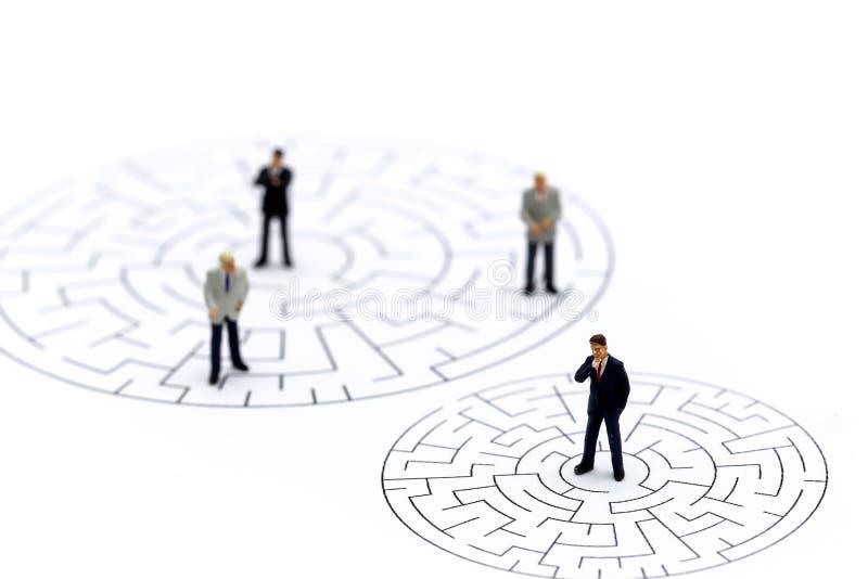 Miniaturleute: Geschäftsmann, der im Anfangspunkt des Labyrinths steht, stockbilder