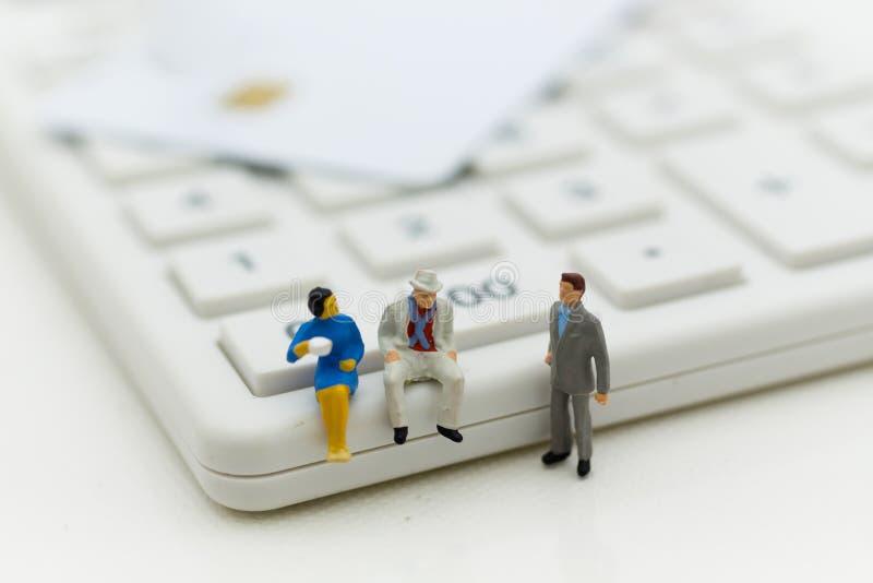 Miniaturleute: Geschäftsmann, der jährlich auf Taschenrechner für Rechengeld, Steuer, monatlich/sitzt Bildgebrauch für Finanzieru stockbild