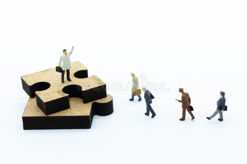 Miniaturleute: Geschäftsmann, der mit Puzzlestücken steht Bildgebrauch für Geschäftsvisionskonzept stockfotos