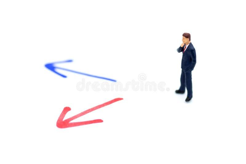 Miniaturleute: Geschäftsmann, der vor Pfeilbahnwahl steht Bildgebrauch für Konzept der unternehmerischen Entscheidung, neu die We lizenzfreies stockfoto