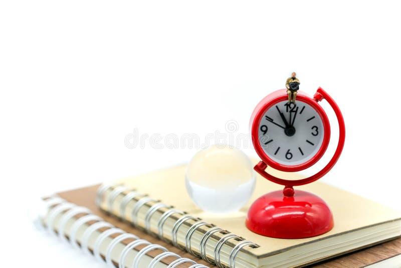Miniaturleute: Geschäftsmann, sitzend auf roter Uhr mit dem Buch lizenzfreie stockbilder