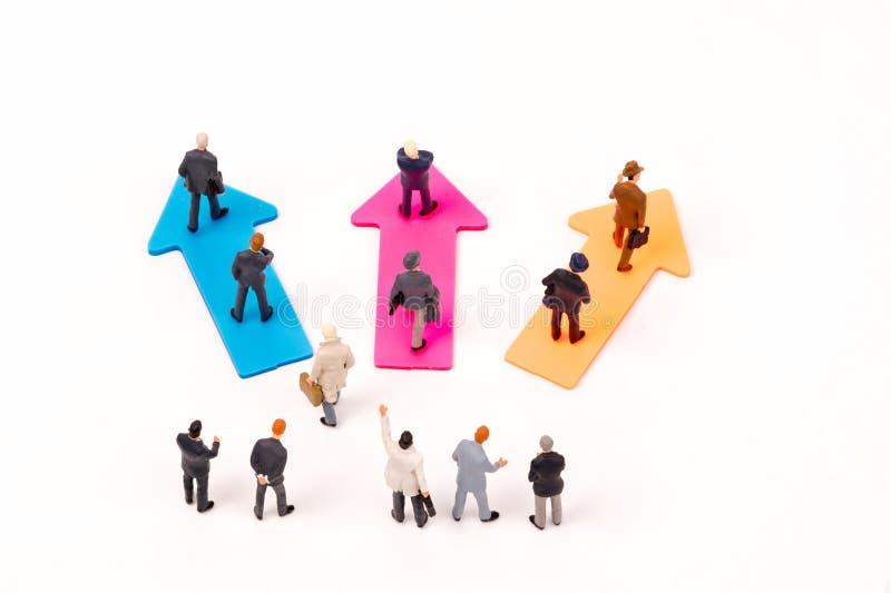 Miniaturleute, Geschäftsmannführer, der auf Pfeil steht stockbilder