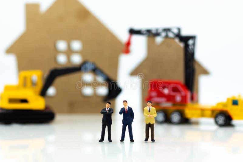 Miniaturleute: Geschäftsmannsitzung für errichtendes Haus Bildgebrauch für Bau, Geschäftskonzept stockfotografie