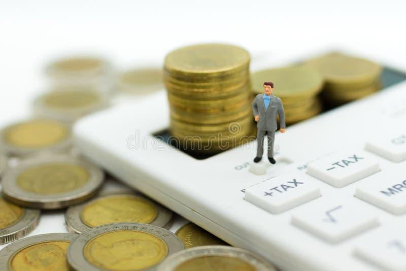 Miniaturleute: Geschäftsmannstand auf Taschenrechner, Berechnungssteuer Monats/jährlich Bildgebrauch für Steuerberechnung jedes J lizenzfreies stockfoto