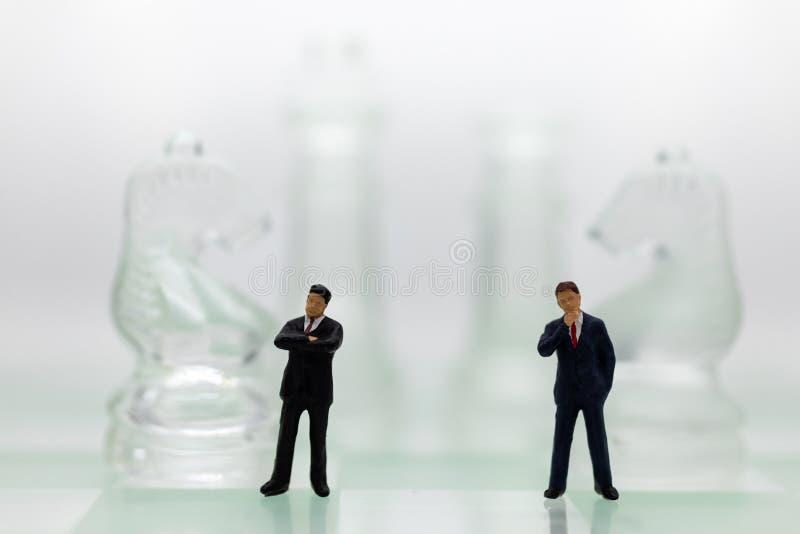 Miniaturleute: Geschäftsmannstellung auf dem Schachspiel, denkende Lösung für das Planspiel, Gebrauch als Geschäftswettbewerb stockfoto