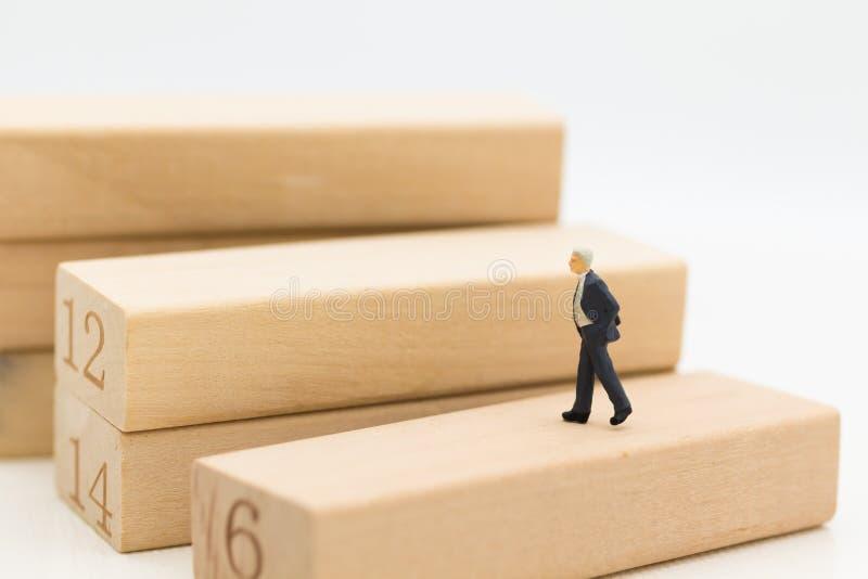 Miniaturleute: Geschäftsmannweg herauf den hölzernen Block Bildgebrauch für Geschäftskonzept stockfoto