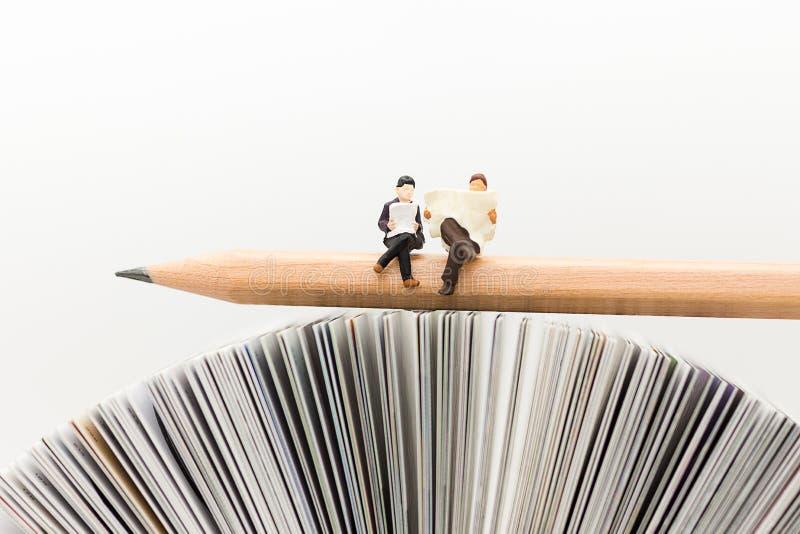 Miniaturleute, Geschäftsteam, das auf Bleistift, Nachrichtenpapier mit als Hintergrundgeschäft lesend, Bildungskonzept sitzt lizenzfreie stockfotografie