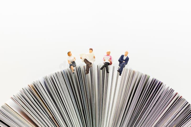 Miniaturleute, Geschäftsteam, das auf Buch, Nachrichtenpapier mit als Hintergrundgeschäft lesend, Bildungskonzept sitzt lizenzfreie stockfotografie