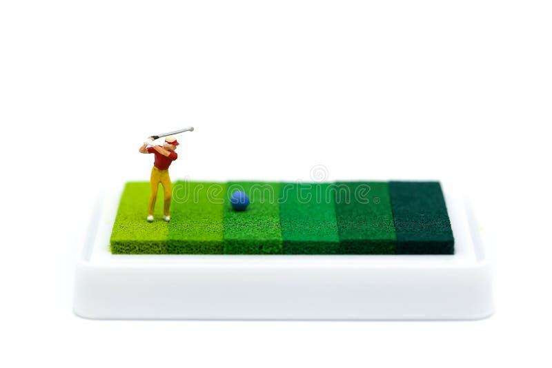 Miniaturleute: Golfspieler, der auf grünem Hintergrund spielt lizenzfreies stockbild