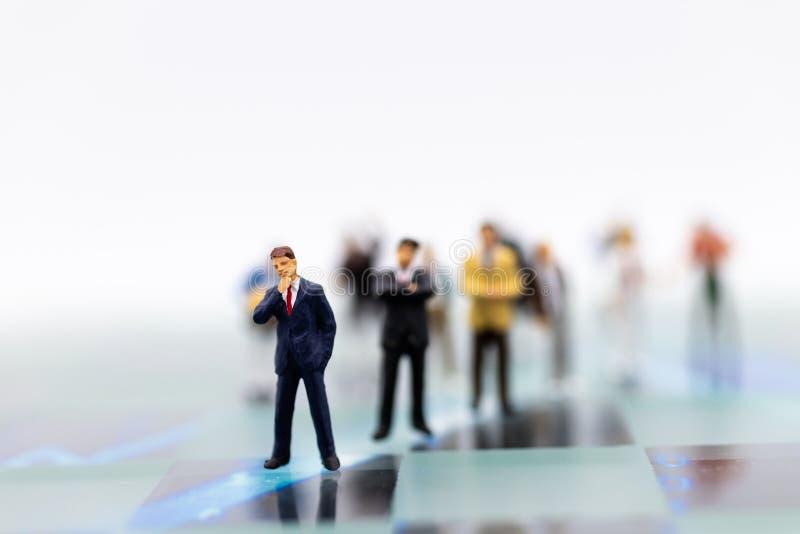 Miniaturleute: Gruppe Geschäftsmannarbeit mit Team Bildgebrauch für Hintergrundwahl des bestgeeigneten Angestellten, Stunde, Job stockfotografie