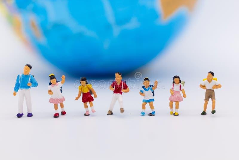 Miniaturleute: Gruppenkinder, die mit Weltkarte stehen Bildgebrauch für Studie International, zurück zu Schulkonzept stockbilder