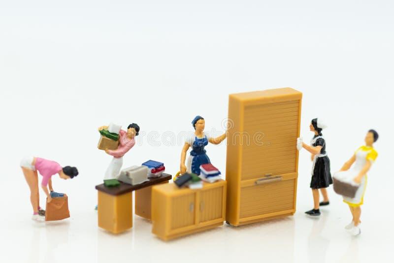 Miniaturleute: Hausfrauen stellen Wäscherei - bügelnd, rentables Geschäft an Bildgebrauch für Hausarbeit, Geschäftskonzept lizenzfreies stockfoto