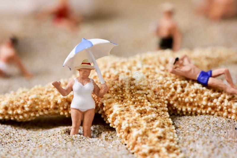 Miniaturleute im Badeanzug auf dem Strand lizenzfreies stockbild