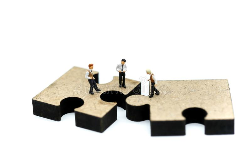 Miniaturleute: junger Geschäftsmann, der auf Puzzlen p steht stockfotos