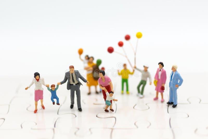 Miniaturleute: Kinder, die zusammen mit Familie spielen Bildgebrauch für internationales Konzept der glücklichen Familie Tages stockfotografie
