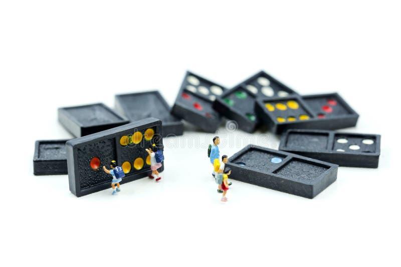 Miniaturleute: Kinder und Student mit dem Domino, spielend und lizenzfreie stockfotos