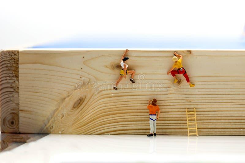 Miniaturleute : kletternde Leitern, zum an die Spitze des PO zu gelangen stockfoto