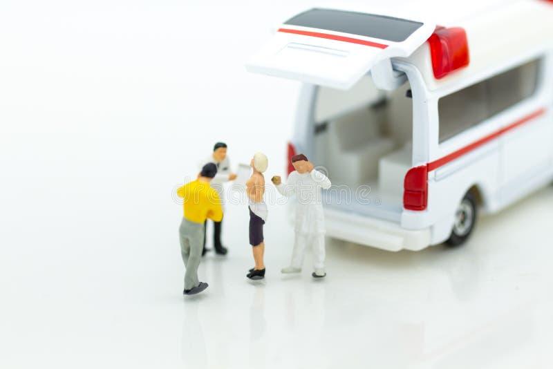 Miniaturleute: Krankenwagen für Behandlung von Patienten weit von medizinische Anlagen Bildgebrauch für Gesundheitswesenkonzept lizenzfreie stockfotos