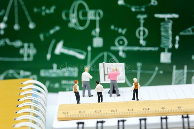 Miniaturleute: Lehrer und Kinder mit Buch und Schulbac stockbild