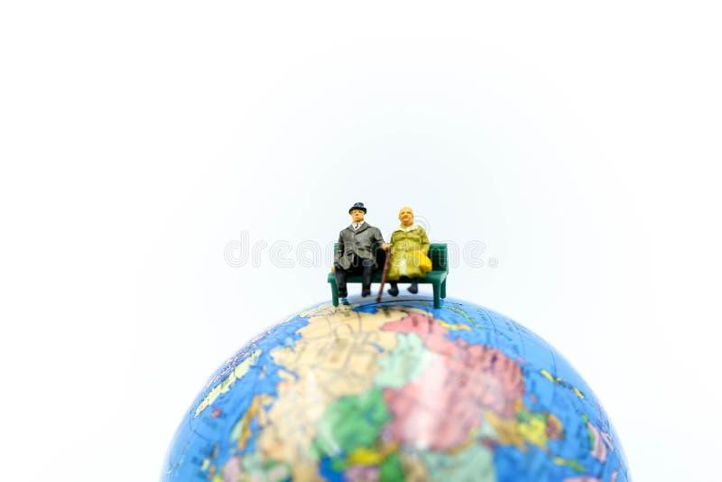Miniaturleute: Liebespaare mit Kugelweltkarteballon zurück stockfotografie