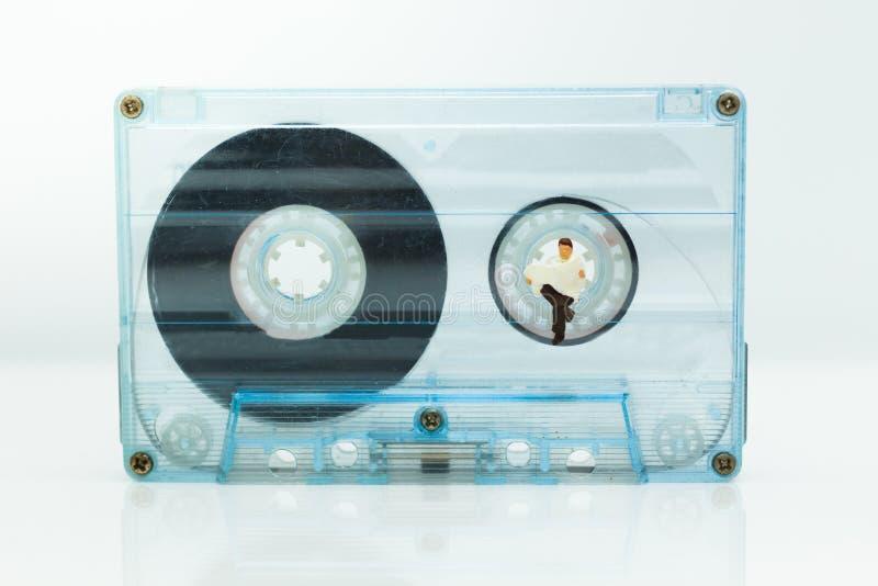 Miniaturleute: Mann sitzen und Lesezeitung auf kompakter Kassette Bildgebrauch für Musik, Geschäftskonzept stockfoto